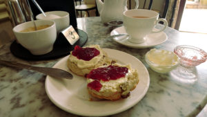 A fruit scone with clotted cream and strawberry jam, with  a cup of green tea in the background.